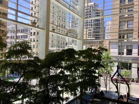 [Photo : hall d'un immeuble avec rue en transparence]